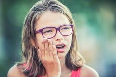 Porträt des Mädchens des jungen jugendlich mit Zahnschmerzen Mädchen mit zahnmedizinischen Klammern und Gläsern stockfotos