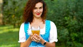 Porträt des Mädchens im bayerischen Kostüm, das Bier hält stock footage