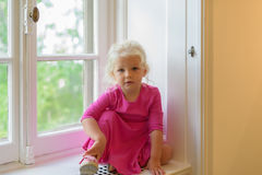 Porträt des Mädchens im rosa Kleid, das auf Fensterbrett sitzt Stockfotografie