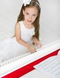 Porträt des Mädchens im weißen Kleid, das Klavier spielt Stockfotografie