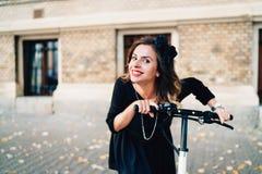 Porträt des Mädchens lächelnd und elektrischen Roller reiten Stockfotografie