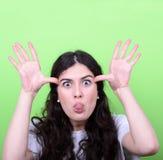 Porträt des Mädchens mit lustigem Gesicht gegen grünen Hintergrund Stockbilder