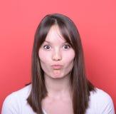 Porträt des Mädchens mit lustigem Gesicht gegen roten Hintergrund Stockbild