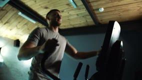 Porträt des männlichen Athleten, der an seinen muscules auf Cross-Trainer in der Turnhalle arbeitet stock video footage