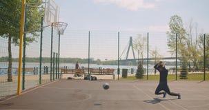 Porträt des männlichen Basketball-Spielers des sportlichen attraktiven Afroamerikaners, der einen Ball in ein Band wirft und seie stock footage