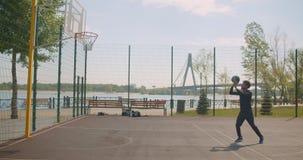 Porträt des männlichen Basketball-Spielers des sportlichen glücklichen Afroamerikaners, der einen Ball in ein Band wirft und mit  stock video