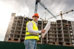Porträt des männlichen Ingenieurs im Hardhat und der Sicherheit mit den Plänen, die gegen Arbeitsbaukräne stehen stockfotografie