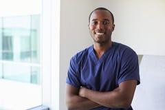 Porträt des männlichen Krankenschwester-Wearing Scrubs In-Prüfungs-Raumes lizenzfreie stockfotos