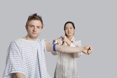 Porträt des männlichen Patienten mit Doktor, der ihn für eine Blutprobe vorbereitet Lizenzfreies Stockbild