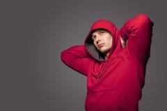 Porträt des männlichen starken gebräunten kaukasischen Mannes in rotem Kapuzenpulli J Lizenzfreies Stockbild