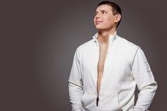 Porträt des männlichen starken gebräunten kaukasischen Mannes in weißem Jacke Lizenzfreies Stockfoto