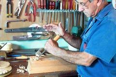 Porträt des Möbeltischlers ein Stück Holz mit Meißel schnitzend und Stockbild
