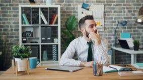 Porträt des müden Kerls arbeitend mit Laptop im Büro, das dann auf Tabelle schläft stock video footage