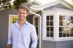Porträt des Mann-stehende Außenseiten-neuen Hauses lizenzfreie stockfotografie