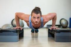 Porträt des Mannes Aerobic-Übung auf Stepper tuend Stockbild
