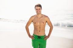 Porträt des Mannes in den Schwimmenkurzen hosen, die auf Strand stehen Lizenzfreie Stockfotografie