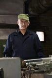 Porträt des Mannes in der grünen Kappe an der Maschine Lizenzfreies Stockbild