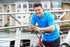 Porträt des Mannes, der Handy während heraus auf Zyklus-Fahrt verwendet lizenzfreie stockbilder
