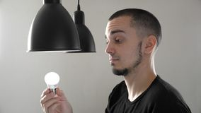 Porträt des Mannes die alte Glühbirne durch eine neue Energiesparende LED-Birne in der Lampe ersetzend r stock video footage