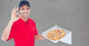 Porträt des Mannes die Pizza liefernd, die OKAYzeichen bei der Stellung gegen grauen Hintergrund gestikuliert Stockfoto