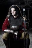 Porträt des Mannes im Ritter Suit With Sword in der alten Kirche, die weg schaut Lizenzfreie Stockfotografie