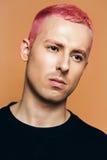 Porträt des Mannes mit dem rosa Haar auf orange Hintergrund Stockfotografie