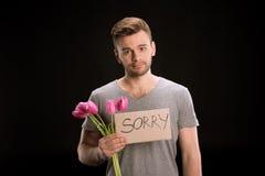 Porträt des Mannes schauend zur Kamera beim Halten des Tulpenblumenstraußes und des traurigen Zeichens Stockfotografie