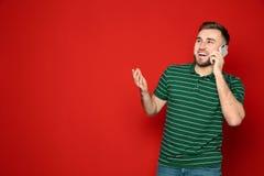 Porträt des Mannes sprechend am Telefon gegen Farbhintergrund stockbild