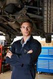 Porträt des Mechanikers Standing Under Car Lizenzfreies Stockfoto
