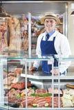 Porträt des Metzgers Standing Behind Counter Lizenzfreies Stockbild