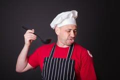 Porträt des missfallenen Kochs mit einem Schöpflöffel in seiner Hand Stockfotos