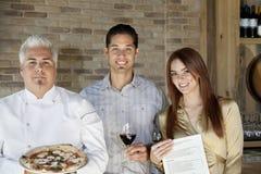 Porträt des mittleren erwachsenen Chefs, der Pizza mit jungen Paaren hält Lizenzfreies Stockfoto