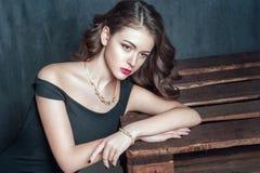 Porträt des Modells mit dem gelockten Haar und Schmuck, Modemake-up, Maniküre auf Nägeln Stockfotografie