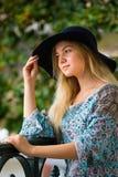 Porträt des modernen blonden Mädchens mit Hut auf Damm am Sommertag Lizenzfreie Stockfotos