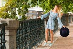 Porträt des modernen blonden Mädchens mit Hut auf Damm am Sommertag Stockfoto