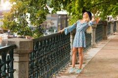 Porträt des modernen blonden Mädchens mit Hut auf Damm am Sommertag Stockfotografie