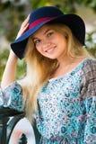 Porträt des modernen blonden Mädchens mit Hut auf Damm am Sommertag Lizenzfreie Stockbilder