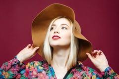 Porträt des modernen erstaunlichen blonden Modells mit dem langen Haar im bunten Hemd und im Hut auf rosa Hintergrund Sinnliche J Stockfotos