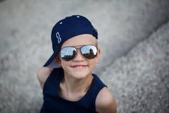 Porträt des modernen kleinen Jungen in der Sonnenbrille und in der Kappe kindheit Lizenzfreie Stockfotografie