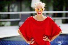 Porträt des modernen recht weiblichen Modells, das roten Lippenesprit leckt Stockfoto