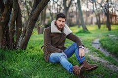Porträt des modischen jungen attraktiven Mannes, der auf grünem Gras I sitzt lizenzfreie stockfotografie