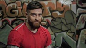 Porträt des muskulösen bärtigen männlichen Mannathleten im roten T-Shirt, das im Kreuzsitz sitzt