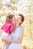 Porträt des Mutter- und Tochterküssens Lizenzfreie Stockbilder