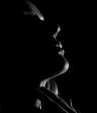 Porträt des nachdenklichen Mädchenprofils der schönen Sinnlichkeit mit geschlossenen Augen in einer Dunkelheit, auf einem schwarz Stockfotografie