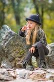 Porträt des nachdenklichen Mädchens in einem schwarzen Hut mit den Ohren und sonnigem Tag des schwarzen Kleidungsfrühlinges Stockfoto