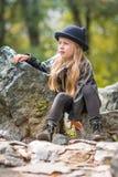 Porträt des nachdenklichen Mädchens in einem schwarzen Hut mit den Ohren und sonnigem Tag des schwarzen Kleidungsfrühlinges Stockfotografie
