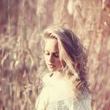 Porträt des nachdenklichen schönen blonden Mädchens auf einem Gebiet im weißen Pullover, dem Konzept der Gesundheit und Schönheit Lizenzfreies Stockbild