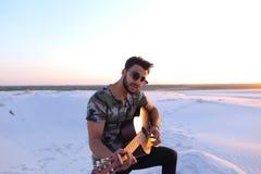 Porträt des Nahaufnahmeporträts des arabischen Kerls, der Gitarre strin spielt Stockfotos