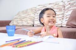 Porträt des netten asiatischen thailändischen Lächelns und des Malens des kleinen Mädchens des c Stockfotos