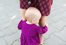 Porträt des netten Babys die Beine der Mutter halten Stockfoto